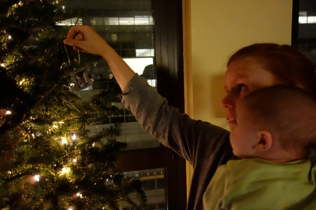 Henry and mom hang his first ornament.