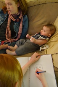 Henry listens to Ona's reading voice while Kaylie draws his portrait.