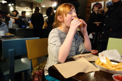 Kaylie demolishes her first Shack Burger at Shake Shack.