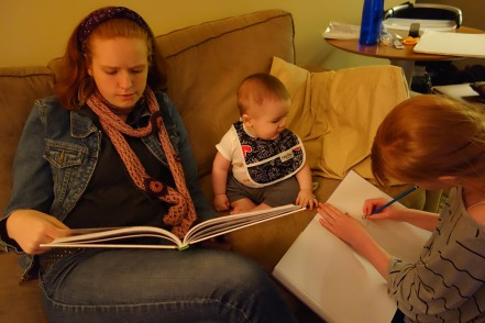 Ona reads to Henry while Kaylie draws him. He is getting plenty of attention.