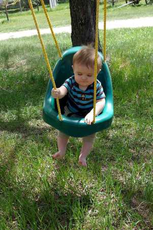 Henry swings on my grandma's swing set.