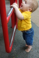 Henry is eager to be able to climb up the bars, but it is a little too early yet.