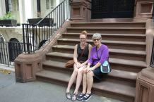 Ona and Gram sit on a brownstone stoop in Brooklyn Heights.