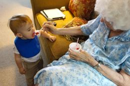 Great-grandma Virgie feeds Henry a bite of her snowball.