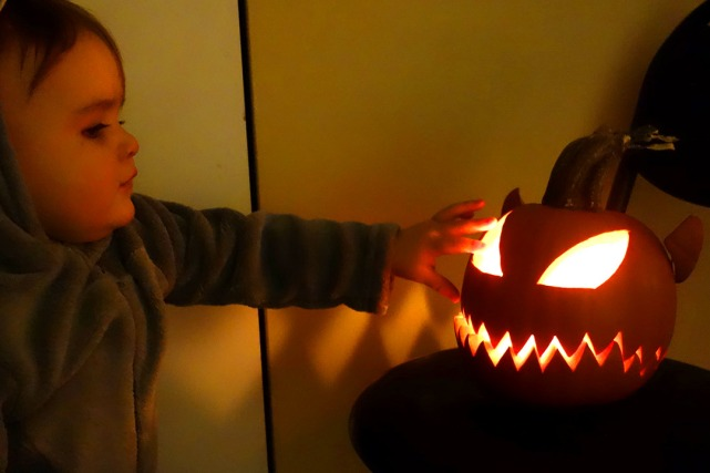 Henry tries to stick his hand in the flame of the jack-o'-lantern.