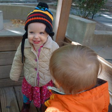 Mae and Henry play in the wooden train at the park.