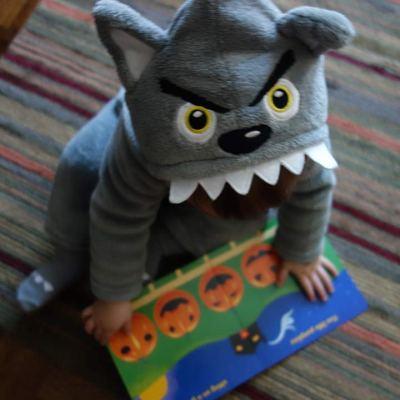 """Henry flips through """"Five Little Pumpkins"""", his Halloween-themed book."""
