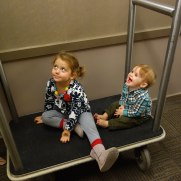 Madison and Henry play in the hall on the luggage cart.