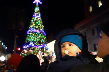 Henry in front of the tree after it is lighted.