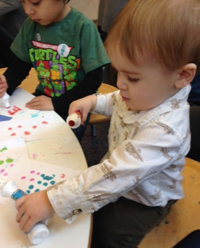 Henry plays with dot paint.