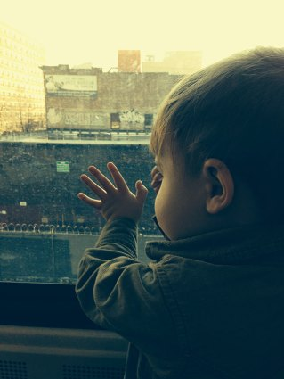 Henry looks out the window in Harlem on Metro-North.