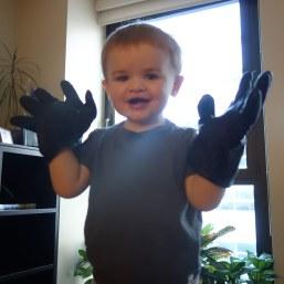 Big hands: Henry in dad's gloves.