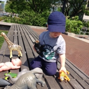 Henry plays with the toy giraffe and tiger.
