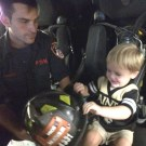 Firefighter Patrick shows Henry his helmet