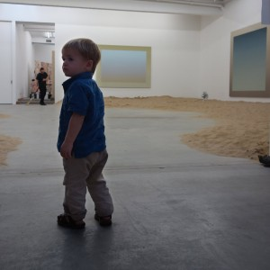 "Henry resists the urge to play in the sand on the gallery floor beneath Pruitt's ""Suicide Paintings""."