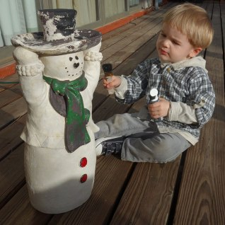 Henry paints a ceramic snowman.